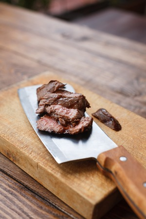 cleaver: Cleaver knife slicing grilled steak on meat cutting wood board