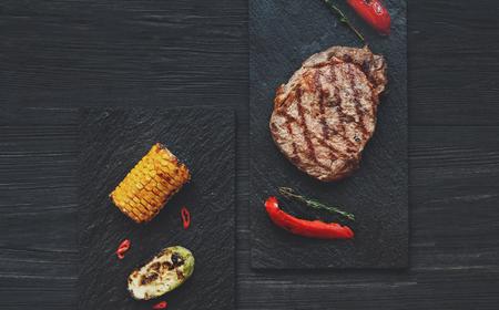 Filete de carne asada a la parrilla sobre fondo de madera oscura de la tabla, vista superior