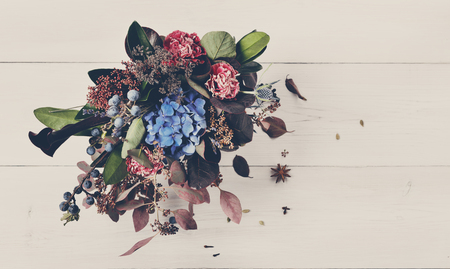 floristic: Beautiful autumn bouquet composition of dried roses and meadow flowers with leaves, floral background. Floristic art decoration closeup, top view with copy space