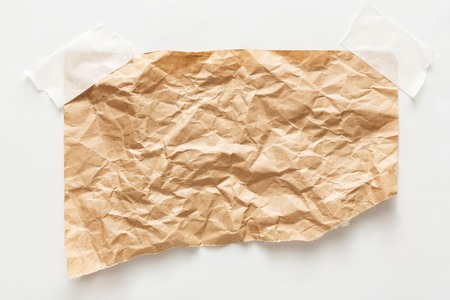 dirty sheet: old craft wrapping paper piece isolated on white background. Aged brown kraft sheet with copy space