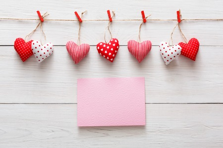 Valentine background with greeting card and diy sewed pillow hearts row border on red clothespins at rustic white wood planks. Happy lovers day card mockup, copy space Stock Photo