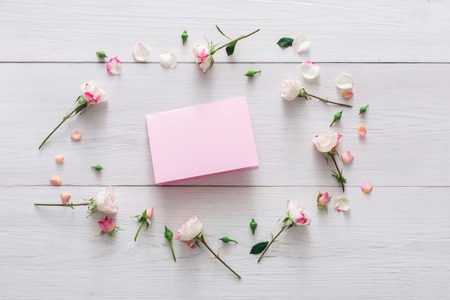 valentine card: Valentine background with pink rose flowers circle and handmade paper card with copy space on white rustic wood. Happy lovers day mockup
