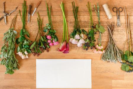 calas blancas: hoja de papel vacío blanco con espacio de copia y ramos de flores y moras en el fondo de madera frescas, vista desde arriba. Rosas y calas de coral Foto de archivo