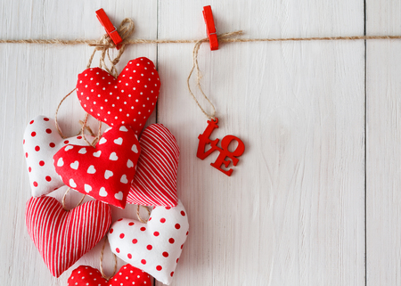 bunch of hearts: Valentine background with sewed pillow diy handmade hearts bunch on red clothespins at rustic white wood planks. Happy lovers day card mockup, copy space Stock Photo
