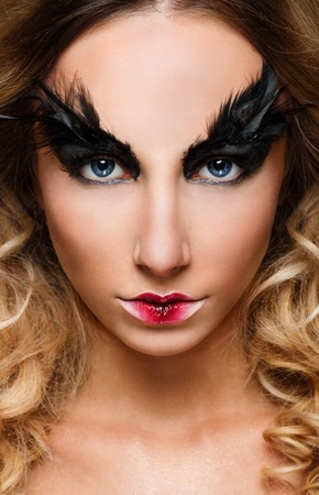 femme fatale: Young pretty woman face with false feather eyelashes, fashion unusual makeup. Closeup glamour girl portrait Stock Photo