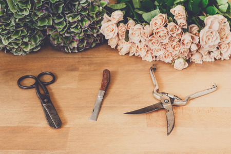 accesories: Florist working tools and accesories, cutting fresh roses for bouquet in flower shop. Floral design studio, making decorations and arrangements. Flowers delivery, creating order