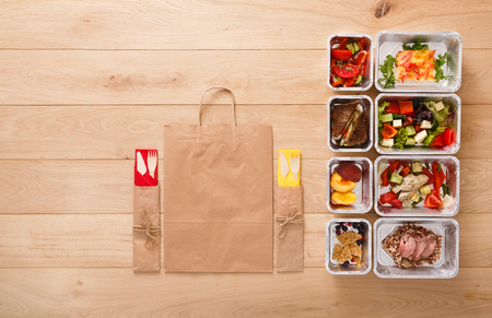 Healthy restaurant food. Chef prepared diet daily meals delivery. Fitness nutrition, vegetables, meat and fruits in foil boxes, cutlery, water and package. Top view, flat lay on wood with copy space Stok Fotoğraf
