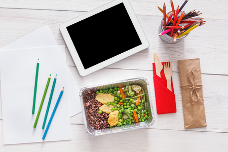 creative artist: Healthy lunch and diet concept. Take away food in foil box, tablet with copy space and pencils on table of creative person, designer or school student. Meat with vegetables, top view on white wood Stock Photo