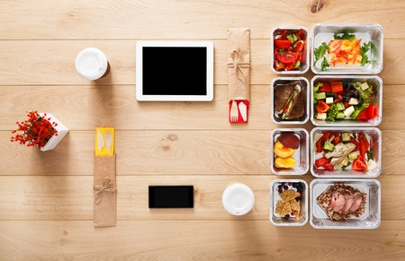 Online healthy restaurant food order, diet plan. Fresh daily meals delivery. Fitness nutrition, vegetable, meat and fruits in foil boxes, coffee and tablet. Top view, flat lay on wood with copy space Stock Photo