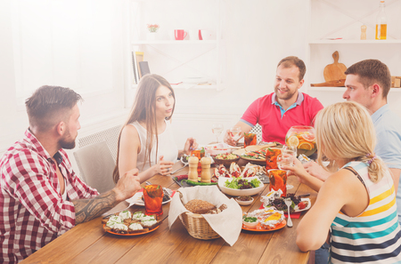 Friends meeting. Group of happy people have friendly conversation, say cheers, laughing at party dinner table in cafe, restaurant. Young company celebrate with alcohol and food on wood Imagens