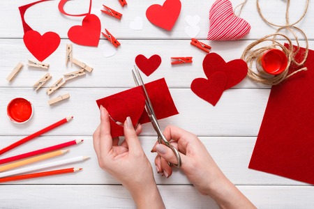 Valentines day holiday scrapbooking background, wedding decorations. Handmade gift greeting heart creating, cut and paste, craft paper, felt and diy tools on white wood. Above view, flat lay Stock Photo