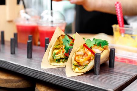 ready to cook food: Street vendor selling taco outdoors. Mexican cuisine snacks closeup, wrapped in craft paper. Fast food for commercial kitchen. Stock Photo