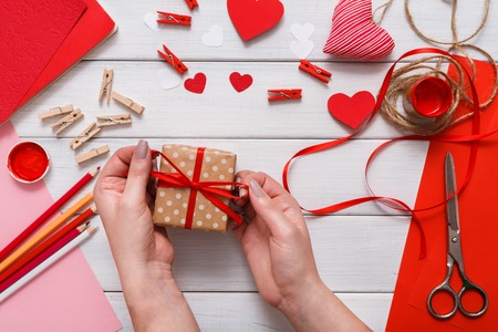 Valentines day holiday handmade or wedding decorations. Wrapping present in gift box, hearts, craft paper, paint and diy tools on white wood. Above view, flat lay