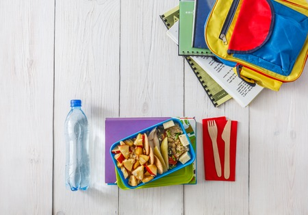 Healthy school lunch for child or teenager, top view, flat lay background with copy space. Pile of exercise books, water, bag and food in lunch box on white wood table, cracker with cheese and apples