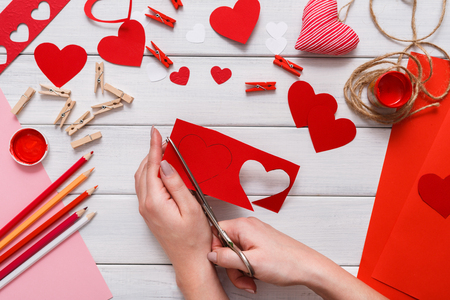 creating: Valentines day scrapbook, wedding or other holiday decorations background. Handmade gift greeting heart creating, cut and paste , craft paper and diy tools on white wood. Above view, flat lay