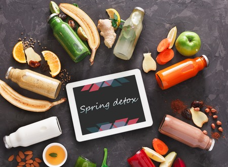 cleanse: Raw juice cleanse diet, spring detox. Healthy smoothie drinks bottles, fruit and vegetable ingredients and tablet with copy space at black background. Top view, flat lay. Internet order online concept Stock Photo