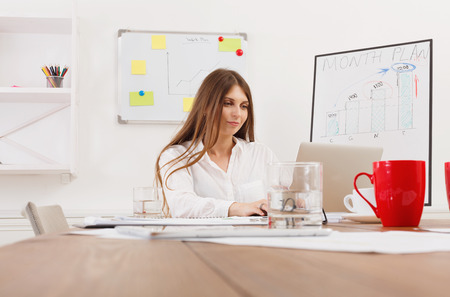 carreer: Beautiful young businesswoman sitting by wooden desk with laptop. Modern office worker in white room interior, red coffee cup on table. Succesfull woman, female carreer concept.
