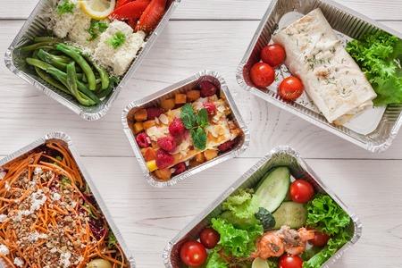 Gezonde voedsel achtergrond. Verwijder natuurlijke organische creatieve maaltijden in folie dozen. Fitness voeding, vlees, kleurrijke groentesalades en fruit. Bovenaanzicht, vlakke lay.
