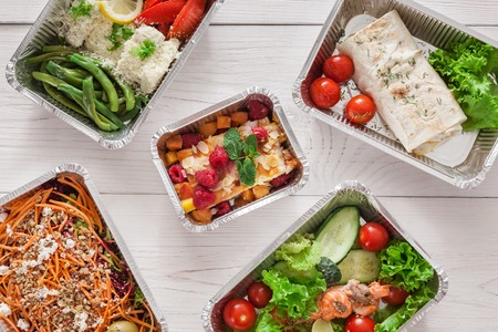 Healthy food background. Take away of natural organic creative meals in foil boxes. Fitness nutrition, meat, colorful vegetable salads and fruits. Top view, flat lay.