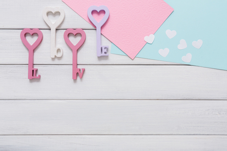 key words art: Key from love. Happy Valentines Day background with heart in keys form, greeting cards and paper letters, pastel pink and violet decorations, copy space on white wood planks
