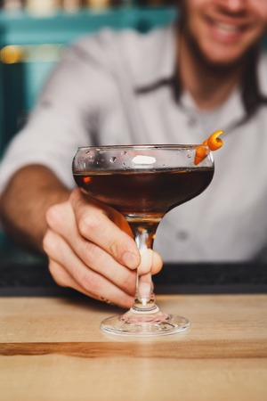 Unrecognizable Barman offers alcohol cocktail in night club. Professional bartender gives drink for party. Focused on glass