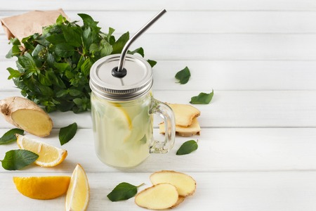 cleanse: Detox cleanse drink, natural lemonade ingredients. Organic healthy juice in glass jar for weight loss diet or fasting day. Mint, lemon and ginger mix on white wood with copy space