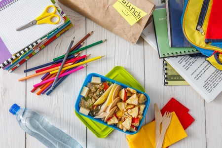 lunch table: Healthy school lunch for child or teenager, top view, flat lay background. Pile of exercise books, water, bag and food in lunch box on white wood table, cracker with cheese and apples