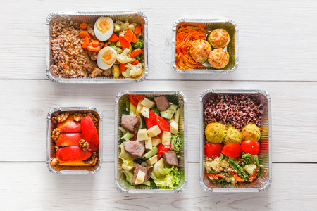 Healthy restaurant food. Chef prepared diet daily meals delivery. Fitness nutrition, vegetables, meat and fruits in foil boxes. Top view, flat lay on wood with copy space