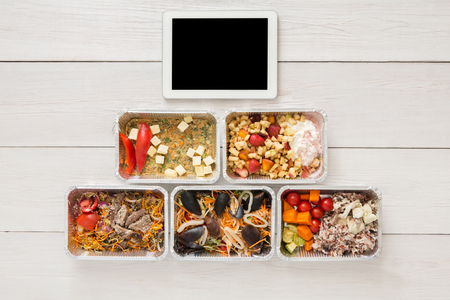 eat right: Healthy restaurant food, mockup for internet online order background. Fresh diet daily meals delivery. Vegetables, seafood, meat and fruits in foil box. Top view, flat lay on wood, copy space Stock Photo