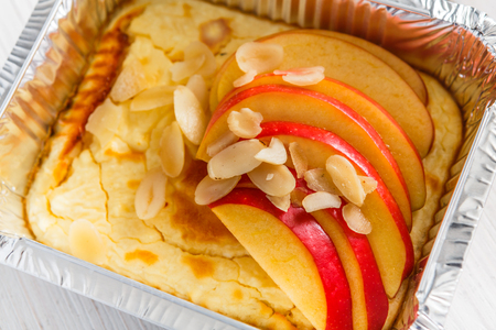 Healthy snack or lunch. Natural food in foil box, diet concept. Cheesecake with apple and almond slices Stock Photo