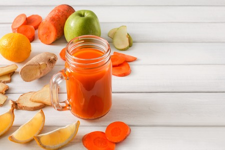 cleanse: Detox cleanse drink, vegetable smoothie ingredients. Natural, organic healthy juice in glass jar for weight loss diet or fasting day. Carrot, apple, ginger and lemon mix on white wood with copy space