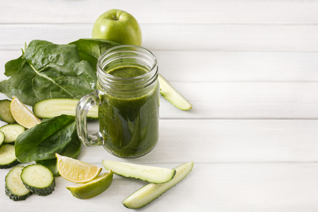 cleanse: Detox cleanse drink, green smoothie ingredients. Natural, organic healthy juice in glass jar for weight loss diet or fasting day. Cucumber, apple, lime and spinach mix on white wood with copy space