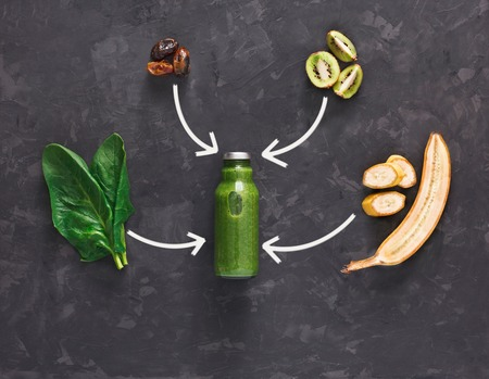 cleanse: Detox cleanse drink concept, green vegetable smoothie ingredients. Natural, organic healthy juice in bottle for weight loss diet or fasting day. Kiwi, banana and spinach mix, flat lay on black
