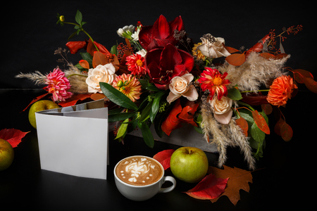 dried flower arrangement: Cappuccino and beautiful flowers composition. Flower shop composition. Coffee cup with foam, apple, fresh and dried flowers bouquet on black wood background. Florist art and floral design concept