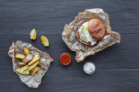 Fast food restaurant dish top view. Meat cheese burger in craft paper, potato chips and wedges. Take away set on dark black wood background. Hamburger and spicy tomato sauce. Stock fotó