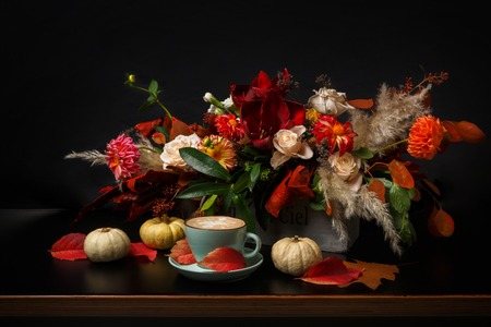 dried flower arrangement: Cappuccino and beautiful flowers still life. Flower shop composition. Coffee cup with foam, apple, fresh and dried flowers bouquet on black wood background. Florist art and floral design concept Stock Photo