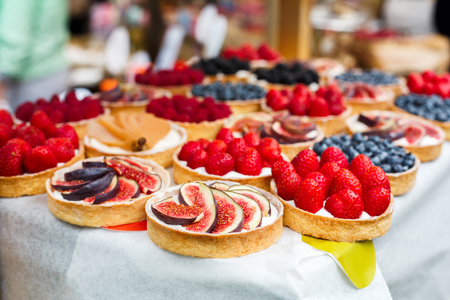 Fruit and berry tarts dessert tray assorted outdoors. Closeup of beautiful delicious pastry sweets with fresh natural strawberries and figs. French Bakery catering. Shallow depth of field Stock Photo