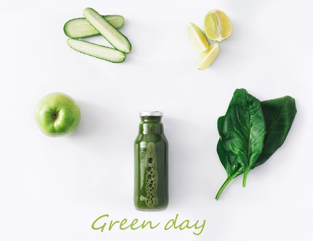 cleanse: Detox cleanse drink concept, green vegetable smoothie ingredients. Natural, organic healthy juice in bottle for weight loss diet or fasting day. Cucumber, apple, lime and spinach mix isolated on white