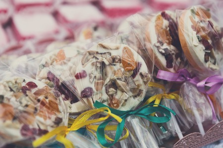 frutos secos: Different caramel lollipops with dried fruits and nuts. Cookies and candies closeup, confectionery sale