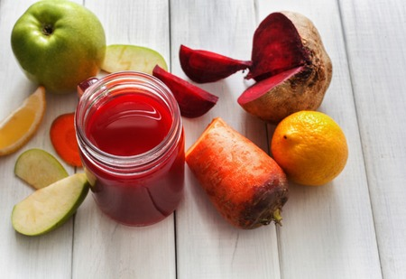 cleanse: Detox cleanse drink, vegetable smoothie ingredients. Natural, organic healthy juice in glass jar for weight loss diet or fasting day. Beetroot, apple, carrot and lemon mix on white wood, copy space