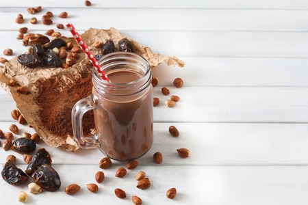 cleanse: Detox cleanse drink, chocolate smoothie ingredients. Natural, organic healthy juice in glass jar for weight loss diet or fasting day. Cocoa powder, nuts, date fruit mix on white wood with copy space