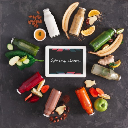 Healthy spring detox drinks with fruit and vegetable ingredients and tablet with copy space on screen at black background. Glass bottles with smoothie, top view, flat lay. Internet order online