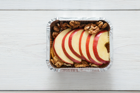 healthy snack: Healthy snack or lunch. Natural food in foil box, diet concept. Apple dessert with walnuts, top view on white wood