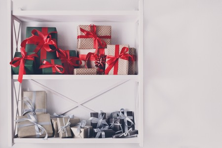 high key: Colorful gift boxes wrapped in paper on white shelves in modern interior. Any holiday background with copy space. Christmas, birthday or valentine concept. High key