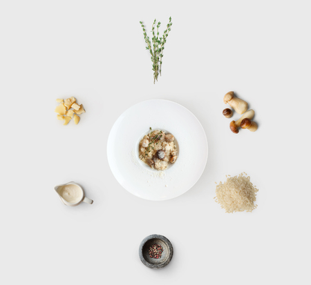 Cooking italian food, risotto with wild mushrooms, isolated on white background. Rice, fungus, sauce, parmesan and other ingredients around plate with dish ready Stock Photo