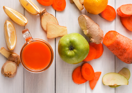 cleanse: Detox cleanse drink, vegetable smoothie ingredients. Natural, organic healthy juice in glass jar for weight loss diet or fasting day. Carrot, apple, ginger and lemon mix on white wood, top view