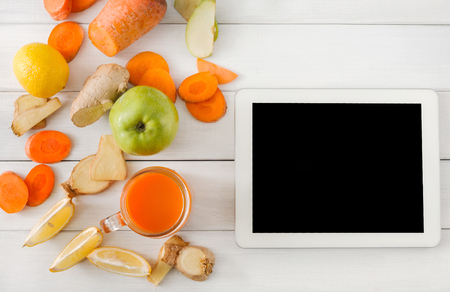 cleanse: Order online detox cleanse drink, vegetable smoothie ingredients. Natural, healthy juice in glass jar. Carrot, apple, ginger and lemon mix on white wood with tablet screen for copy space, top view