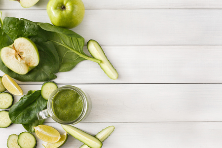 cleanse: Detox cleanse drink background. Green smoothie ingredients. Natural healthy juice in glass jar for diet or fasting day. Cucumber, apple, lime and spinach mix on white wood top view with copy space