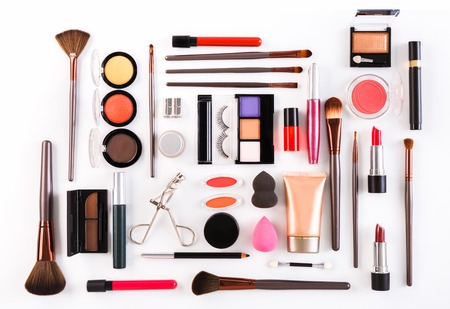 Makeup cosmetics, brushes and other essentials on white background. Top view, flat lay. Multicolored beauty tools and products collection, lipsticks, eyeshadow, mascara, sponge, eyelashes and more Banco de Imagens