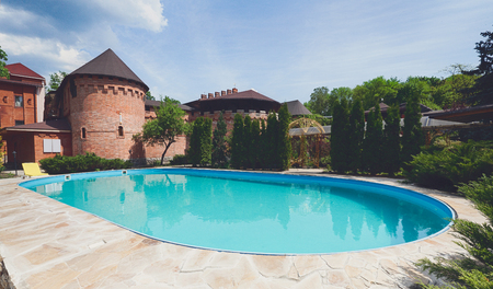 Luxury swimming pool beside the hotel in medieval british castle style. Landscape design of resort territory. Blue water in summer park.